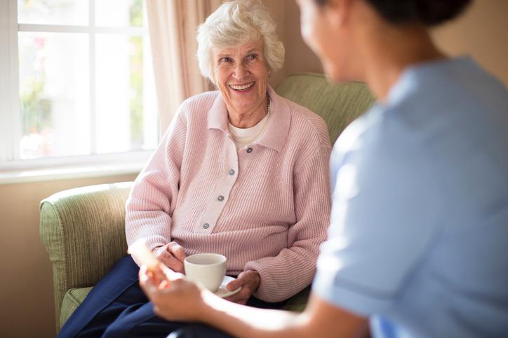 Nurse and patient drinking tea on sofa
