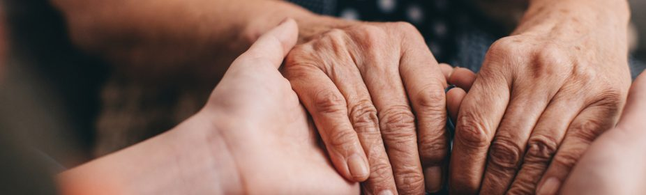 Hands of young person holding the hands of an older adult