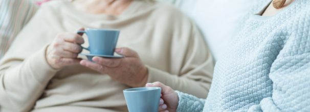 Two elderly women drinking coffee during conversation at home