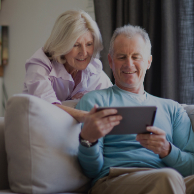 Elderly couple reading mobile tablet device